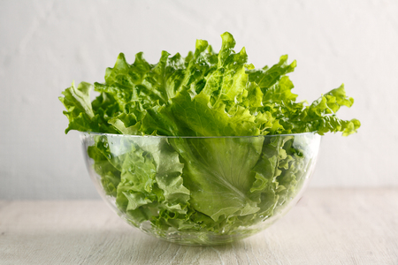 lettuce leaves in glass bowl on white background