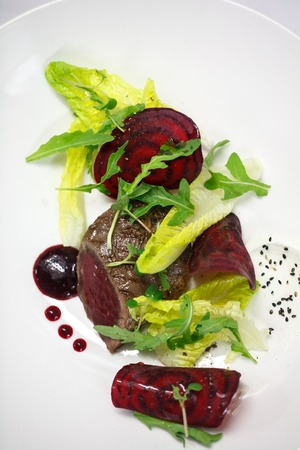 marinated beef with beet and sauce from cranberry on white plate for restaurant menu