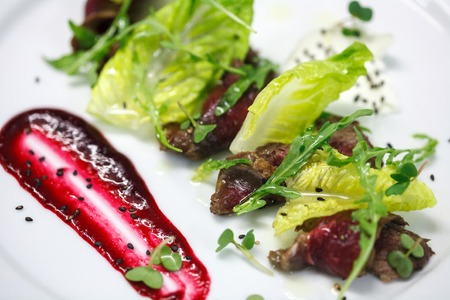 marinated slices of beef with cranberry sauce on white plate for restaurant menu Stock Photo
