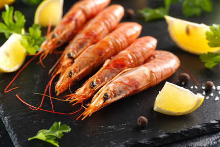langoustines with spices, lemon and herbs on a black background. Tiger prawns with spices and lemon. Closeup