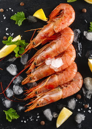langoustines or shrimps with spices, lemon and herbs on a black background. Top view. Flatlay