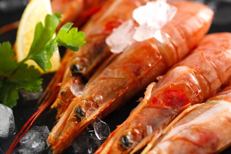 langoustines or shrimps with spices, lemon and herbs on a black background. Closeup Banque d'images