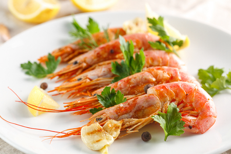 Grilled shrimps with spice, lemon and greenery on white plate. Grilled seafood. 写真素材