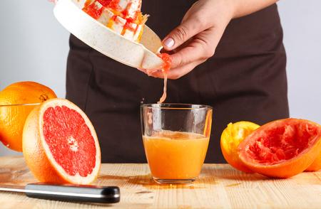 the girl prepares fresh squeezed citrus juice. Grapefruit and orange