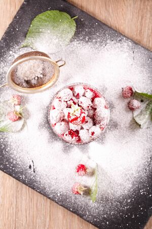 delicious dessert of fresh raspberries and strawberries with oatmeal in a glass glass. Verin. All sprinkled with powdered sugar and decorated with fresh berries
