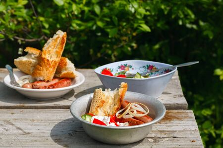BBQ. Village lunch. grilled sausages with vegetable salad, onion and bread. In a metal plate, on a wooden table. Rustic style. Top view Stok Fotoğraf