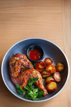grilled chicken with baby potatoes and tomato sauce on metal plate. Top view. Copyspace