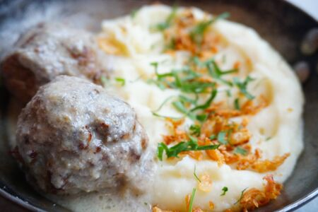 meat balls in sauce with mashed potatoes, French fries and herbs. Closeup Stock Photo