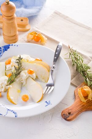 Salad of fresh pears, young cheese, physalis and rosemary on table. Reklamní fotografie