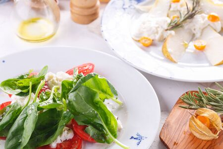 Salads are decorated on white plates for the restaurant menu.