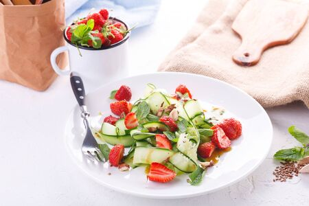 Light summer detox salad with strawberries, cucumber, nuts and flax seeds on white plate