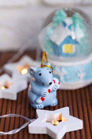 The symbol of the new year is a rat, in the form of a Christmas toy on the background of a Christmas globe