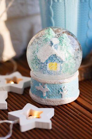 snow Christmas globe with a house inside on the background of a blue mug. Reklamní fotografie