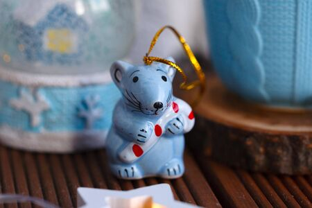 The symbol of the new year is a rat, in the form of a Christmas toy on the background of a Christmas globe and a blue mug