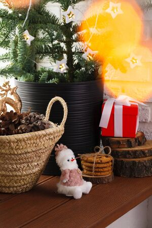 Christmas interior. The wooden windowsill is decorated with a Christmas tree, a wicker basket with cones and Christmas tree toys and garland lights
