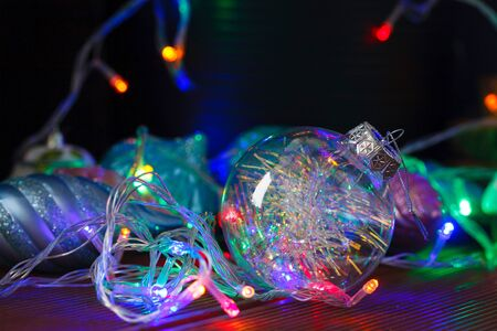 Beautiful transparent Christmas ball with lights from the garlands on dark background