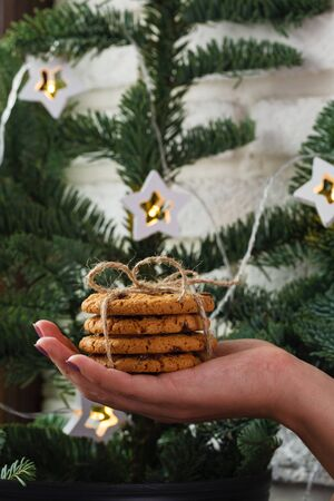 girl holding a bunch of cookies on the background of a Christmas tree