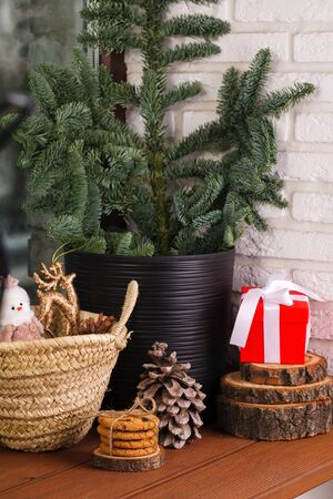 Christmas interior. The wooden windowsill is decorated with a Christmas tree, a wicker basket with toys, cookies and Christmas tree toys Reklamní fotografie