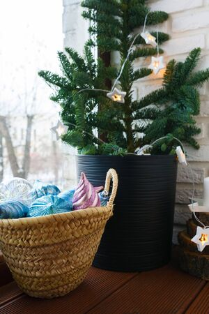 Christmas interior. Window sill decorated with Christmas tree, basket with Christmas toys and garland Reklamní fotografie