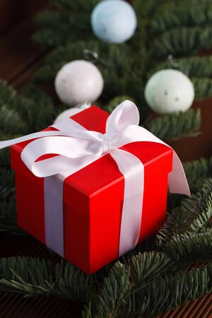 Christmas composition. red gift box lying on a branch of the Christmas tree Reklamní fotografie