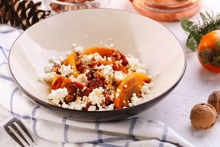 Winter dessert. caramelized persimmon with walnuts and cottage cheese in beige plate. Decorated Reklamní fotografie