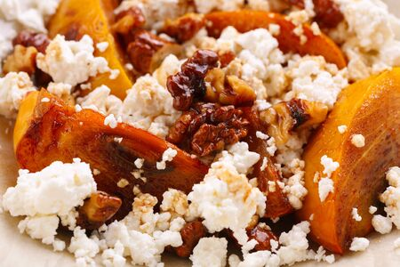 Winter dessert. caramelized persimmon with walnuts and cottage cheese in beige plate. Closeup Reklamní fotografie
