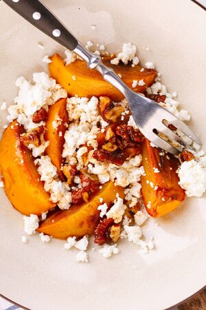 Winter dessert. caramelized persimmon with walnuts and cottage cheese in beige plate. Top view