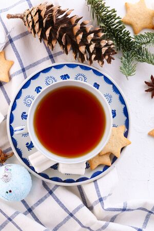 black tea in vintage ceramic mug with ginger cookies and marshmallow. Decorated with cones and spruce branches. Christmas decorations. Top view Reklamní fotografie