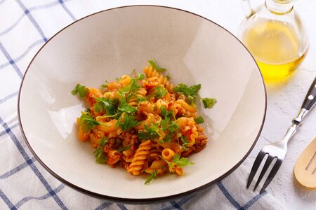 traditional pasta with meat and herbs in a beige plate. top view