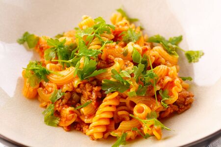traditional pasta with meat and herbs in a beige plate. closeup