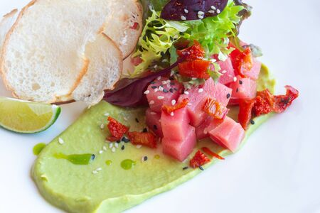 Tuna Tartar with avocado, lettuce, sun-dried tomatoes and bread chips