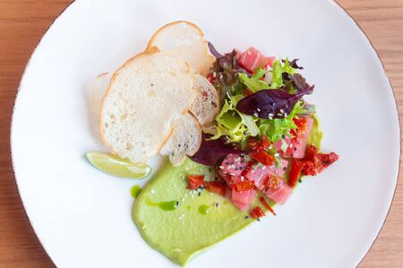 tuna Tartar with avocado, lettuce, sun-dried tomatoes and bread chips on white plate