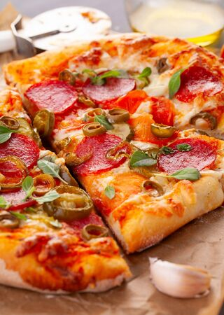 Homemade spicy pepperoni pizza and cooking ingredients. Pepperoni pizza on a gray wooden table. Closeup Фото со стока