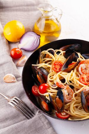 The pasta with seafood. Spaghetti with mussels and tiger prawns, traditional pasta with prawns close-up on a frying pan