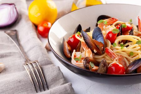 The pasta with seafood. Spaghetti with mussels and tiger prawns, traditional pasta with prawns close-up on a white background Фото со стока