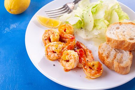 Grilled tiger shrimps in spices, sweet and sour sauce, with lettuce, baguette and lemon. seafood Breakfast. On a blue background