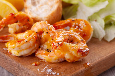 grilled tiger shrimps with spices, sweet and sour sauce, lemon and lettuce Reklamní fotografie - 152069396
