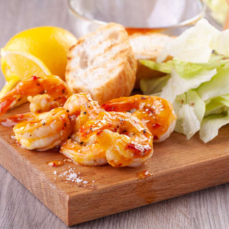 grilled tiger shrimps with spices, sweet and sour sauce, lemon and lettuce