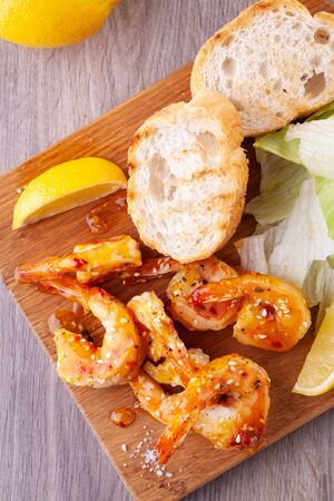 grilled tiger prawns with spices, sweet and sour sauce, lemon and lettuce on a wooden Board. 写真素材