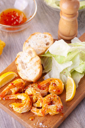 grilled tiger prawns with spices, sweet and sour sauce, lemon and lettuce on a wooden Board. Reklamní fotografie