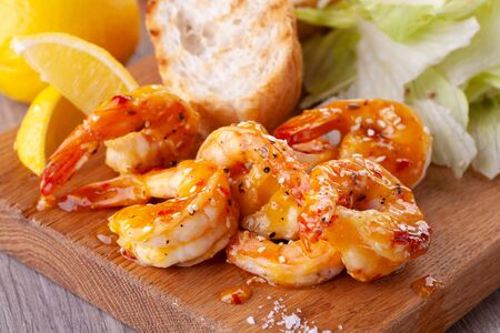 grilled tiger prawns with spices, sweet and sour sauce, lemon and lettuce on a wooden Board. Фото со стока