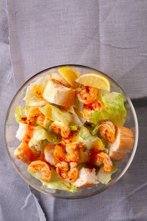 grilled shrimp salad in hot sauce and baguette toast in a glass bowl on a grey textile background Фото со стока