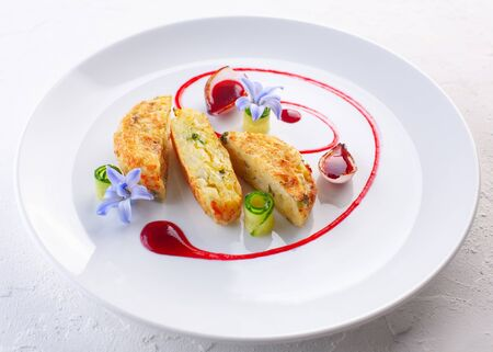 potato pancakes with cranberry sauce on white plate and white background