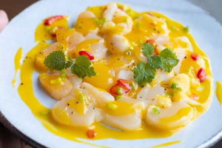 scallop with mango sauce and chili pepper on a white ceramic plate. For the restaurant menu