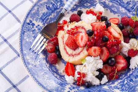 dessert with fresh berries in a blue vintage plate. Sweet roll. Reklamní fotografie - 151978850