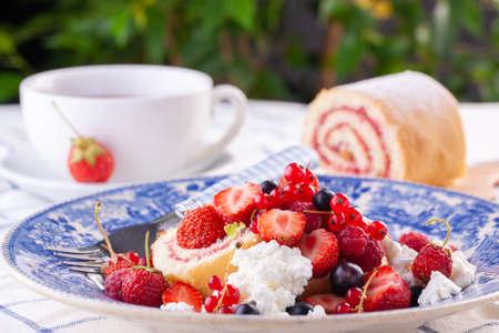 dessert with fresh berries on a white background. Sweet roll Reklamní fotografie - 151979393