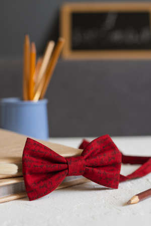 stylish red bow tie on the table, against the background of school supplies-books and pencils. Back to school.