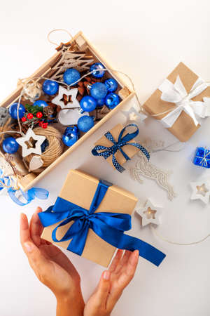 Preparing Christmas gifts. Christmas box in womens hands, blue ribbons, blue balloons on a white background. The view from the top. Reklamní fotografie