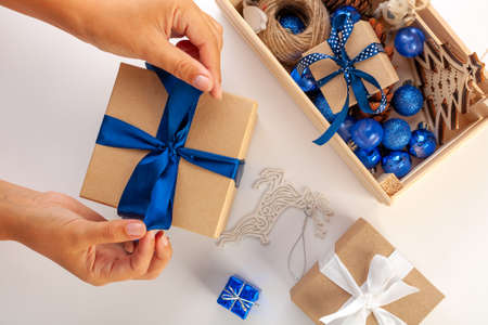 Preparing Christmas gifts. Christmas box in womens hands, blue ribbons, blue balloons on a white background. The view from the top. Stock fotó