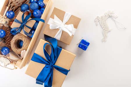 Preparing Christmas gifts. Coffee, Christmas craft boxes, blue ribbons, blue balloons on a white background. The view from the top. Reklamní fotografie